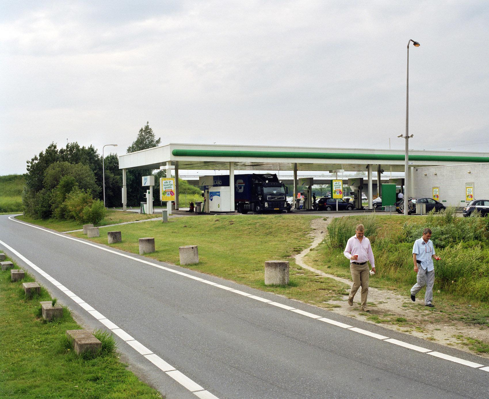 Trampelpfad, der sich neben einer Tankstelle für Fußgänger gebildet hat