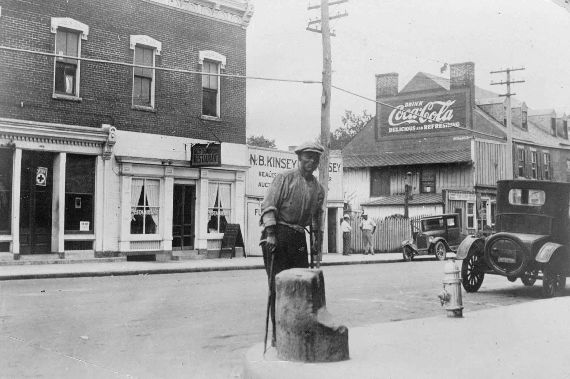 Diese Aufnahme aus dem Jahr 1930 - lange nach der formellen Abschaffung der Sklaverei - zeigt einen ehemaligen Sklaven, der an einem Pfosten angekettet auf einen Job wartet