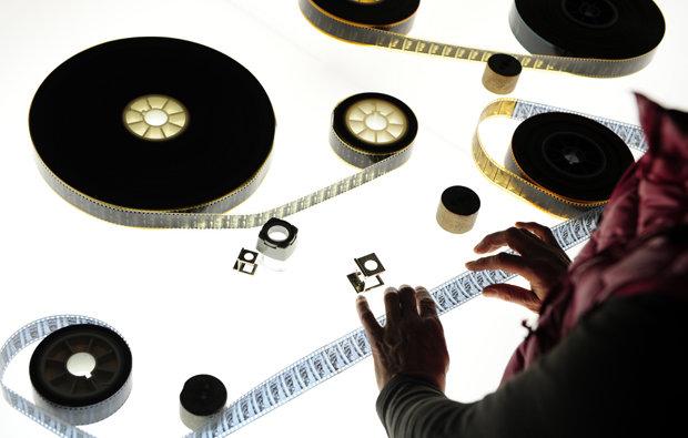 Traditionelle Archivarbeit: Ein Mitarbeiter des deutschen Filminstituts sichtet Material aus der Zeit des 1. Weltkriegs (Foto: Peer Grimm/dpa)