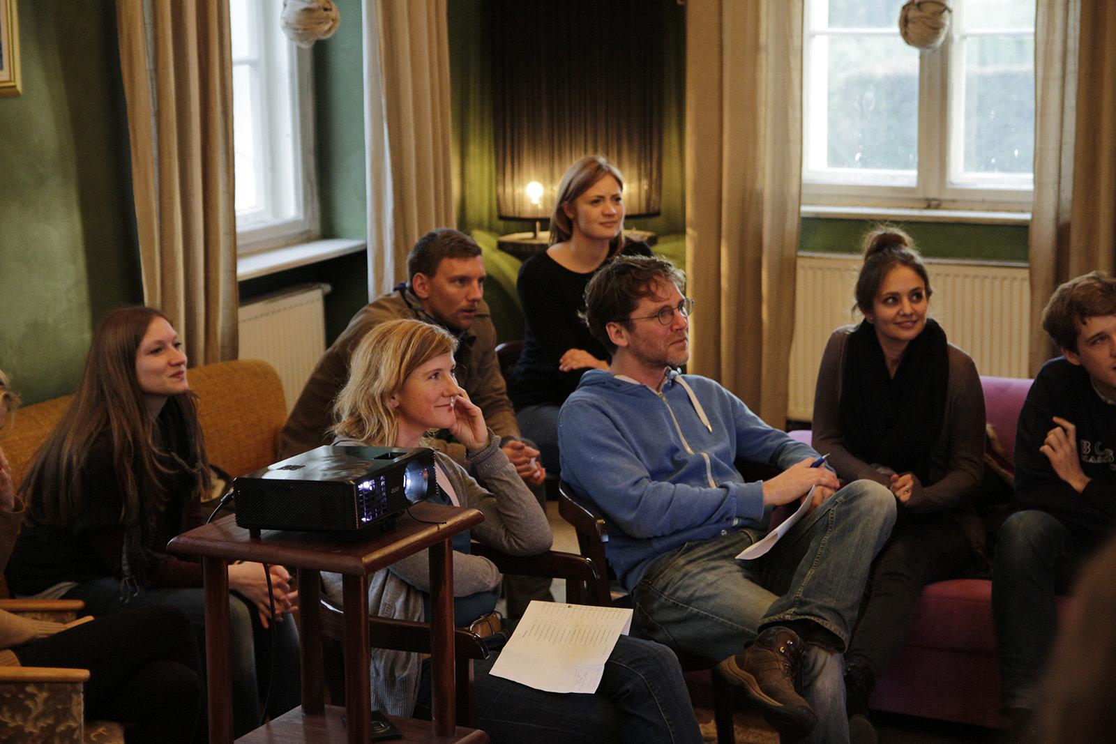 Menschen sitzen zusammen und hören einem Vortrag zu (Foto: Coconat)
