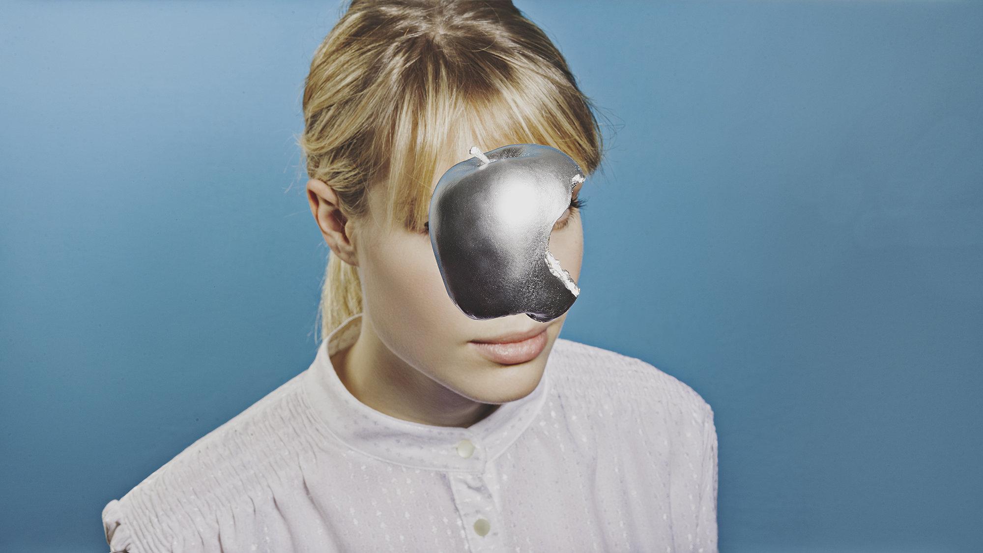 Ein Apfel aus Metall, der dem Marken--Logo von Apple nachempfunden ist, verdeckt das Gesicht einer Frau (Foto: Jan Q. Maschinski)