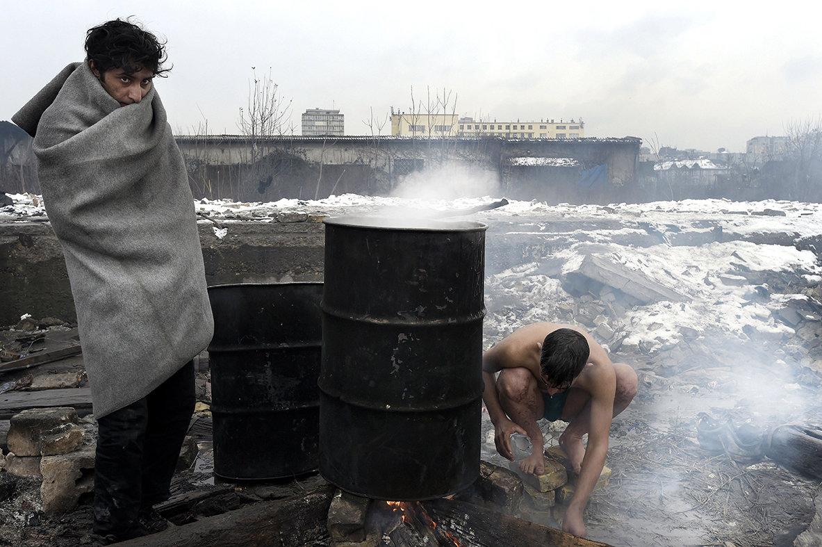 Flüchtlinge in Belgrad erhitzen mit Feuer Wasser in einem Fass (Foto: picture alliance / Photoshot)