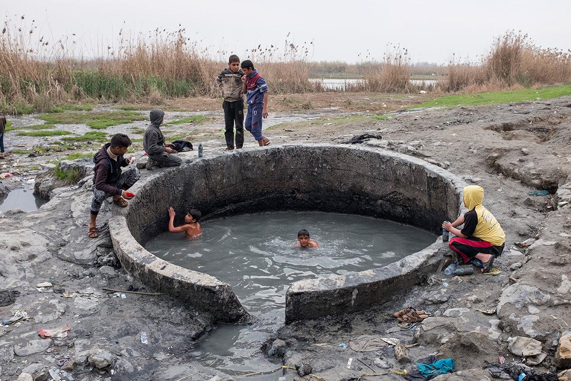 Jungs tauchen in einem Loch nach Schlamm