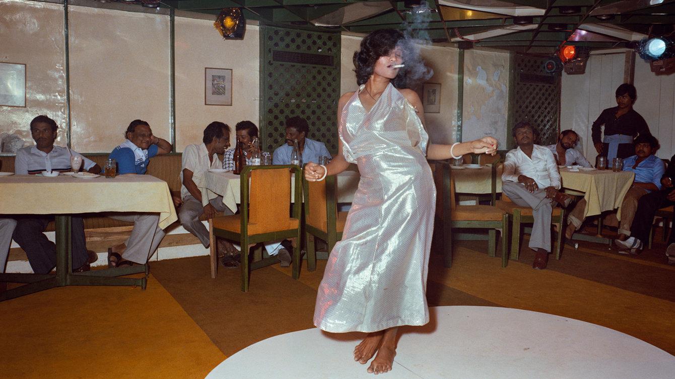 Frau tanzt rauchend vor Männergruppe