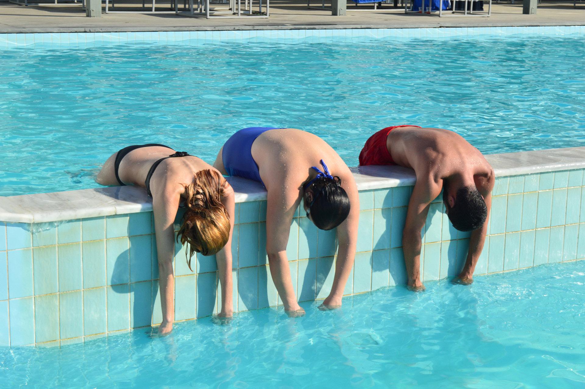 Drei Personen hängen über Schwimmbeckenrand (Foto: Kostis Fokas)