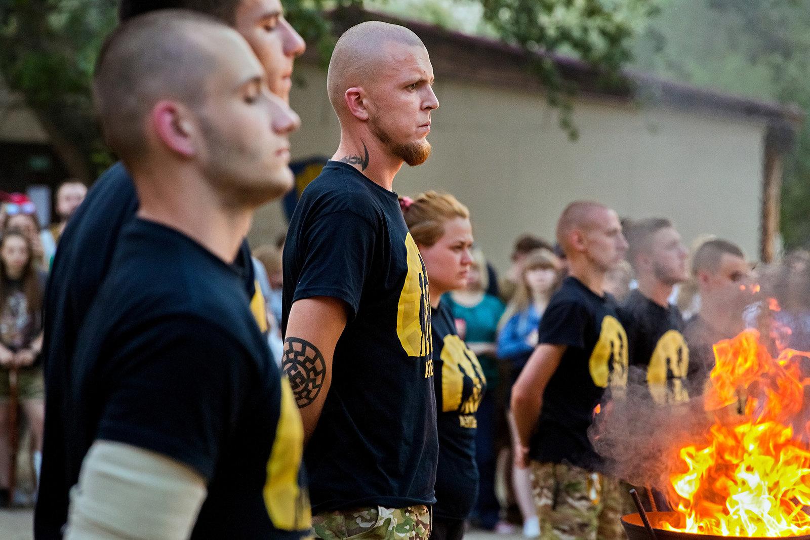 Mehrere Jugendliche stehen am Feuer, sie tragen Asow-T-Shirts