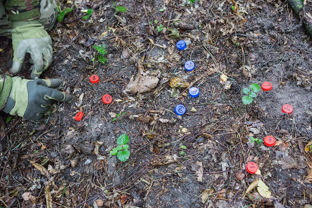 Taktik ist sehr wichtig. Mit Hilfe von Flaschendeckeln auf dem Waldboden wird sie vermittelt. So wird das Vorgehen gegen den Feind vorher geplant.