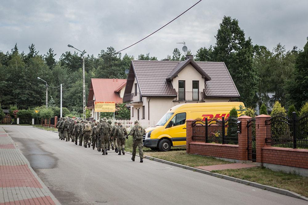 Die paramilitärischen Strzelec marschieren für ihre militärische Übung in einem Wald durch eine Neubausiedlung in Mrozy, ein kleiner Ort rund 1,5 Sunden östlich von Warschau