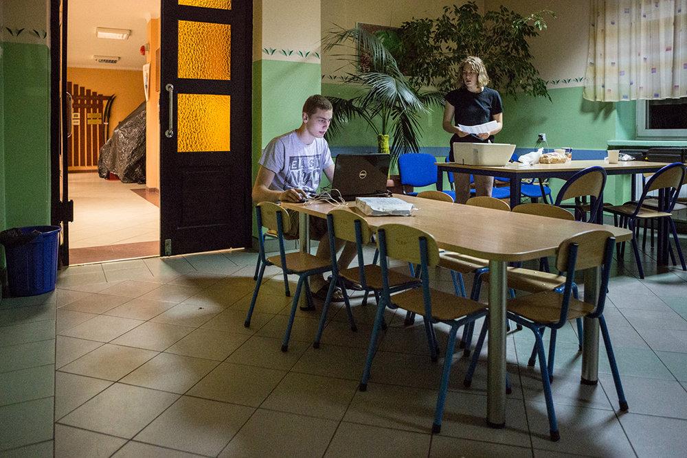 Gosia und ihr Freund bereiten alle Förmichkeiten für das Training im Wald vor. Am Abend zuvor mit Notebook und Drucker in einer Grundschule in Mrozi.