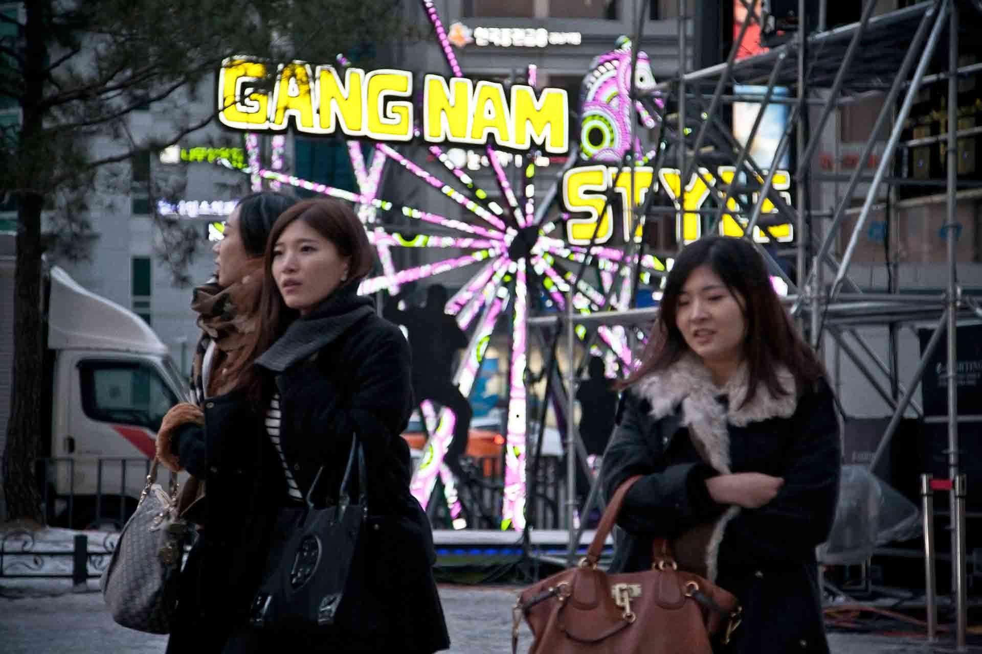 Koreanische Jugendliche in Seoul vor einem Denkmal für den Song Gang Nam Style