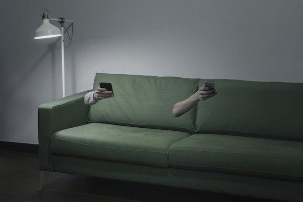 Zwei körperlose Arme halten in einem Wohnzimmer Smartphones in der Hand