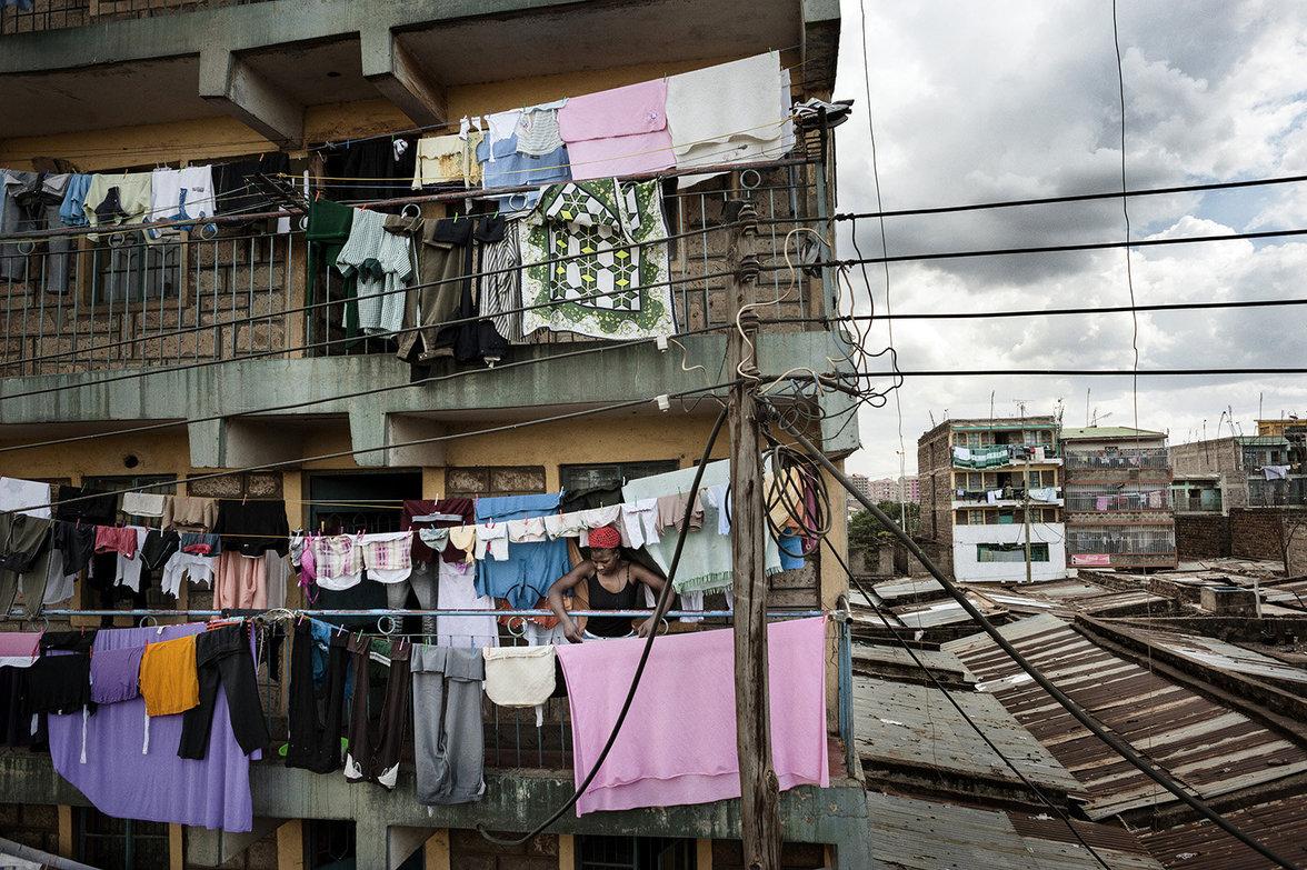 Frau hängt Wäsche auf mit Blick auf eng gebaute Wohnungen