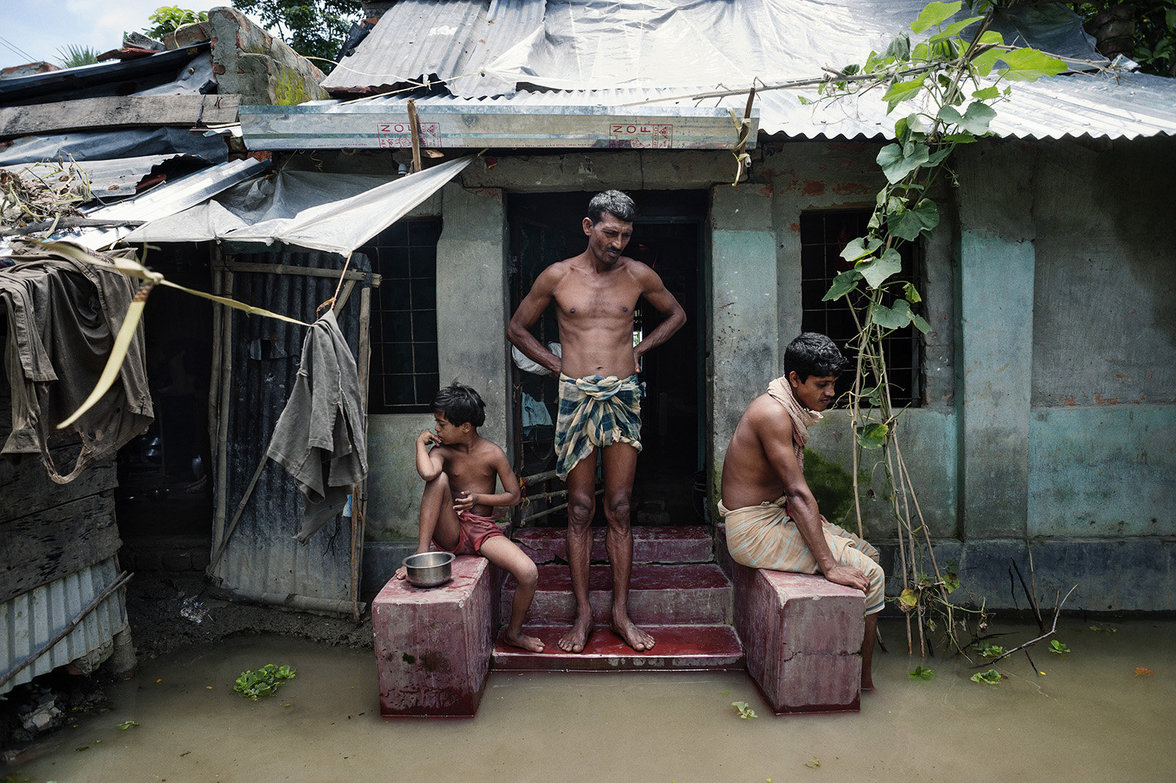 Familie vor ihrem Haus dessen Eingang überschwemmt ist