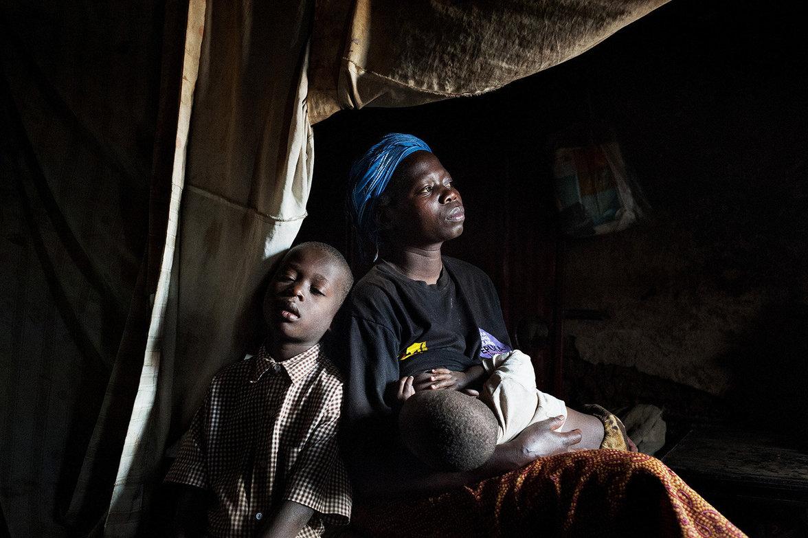 Mutter Rose mit ihrem Sohn und einem Baby an der Brust in ihrer spärlichen Behausung
