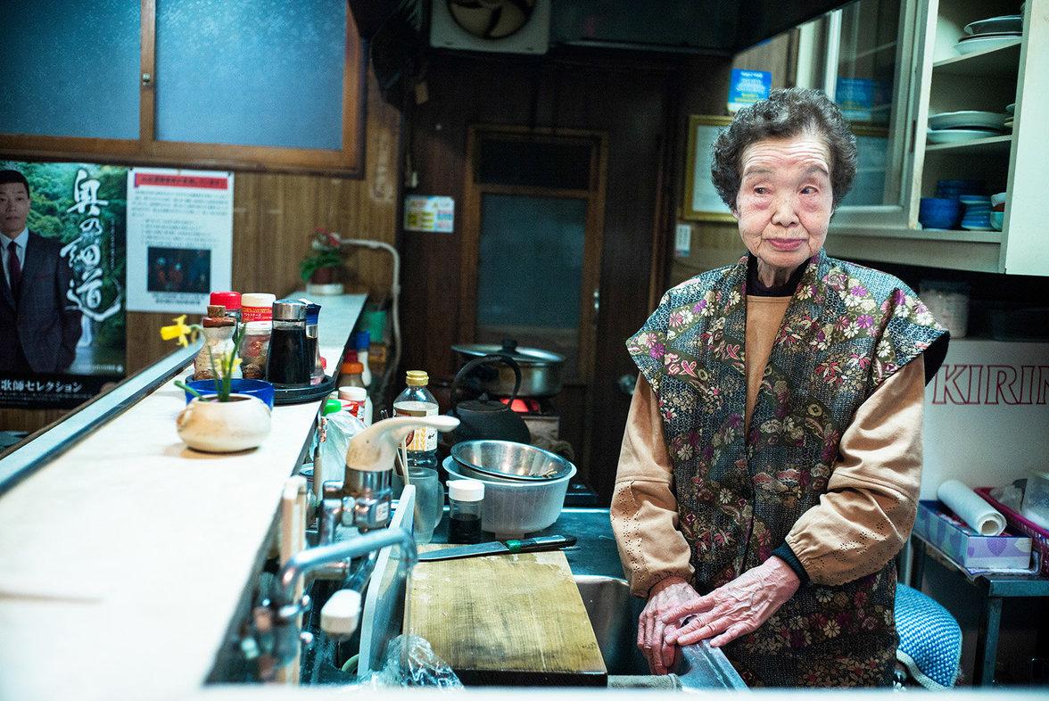 Alte Frau bedient in einem Imbiss in Tokio