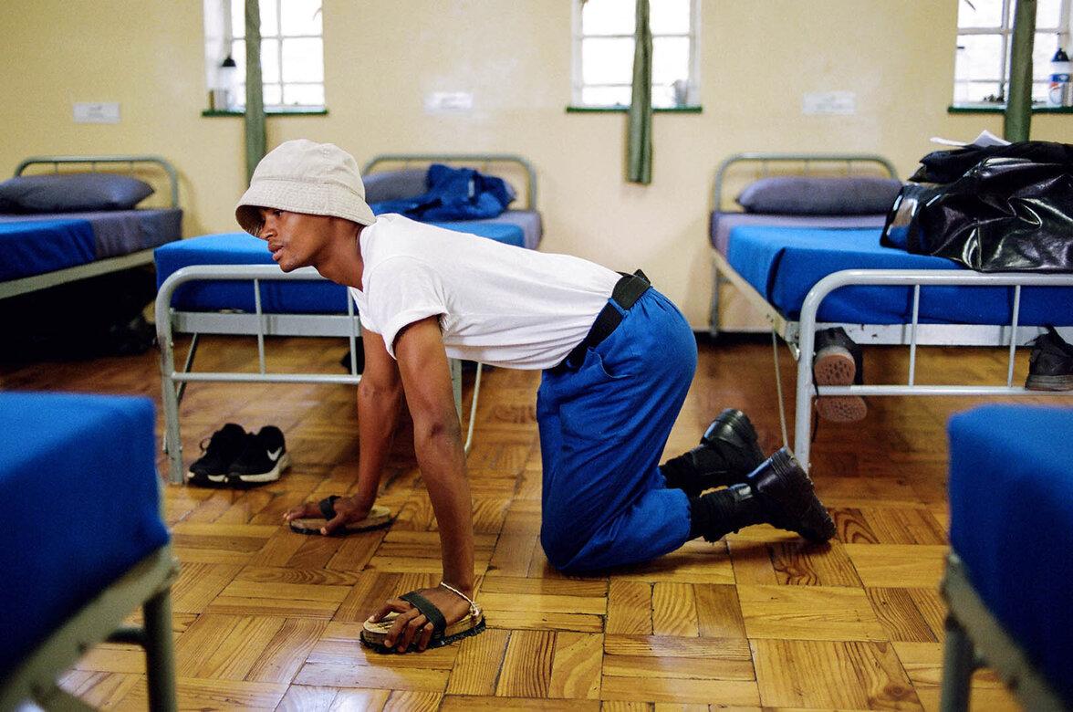 Ein junger Mann schrubbt auf Knien einen Holzboden