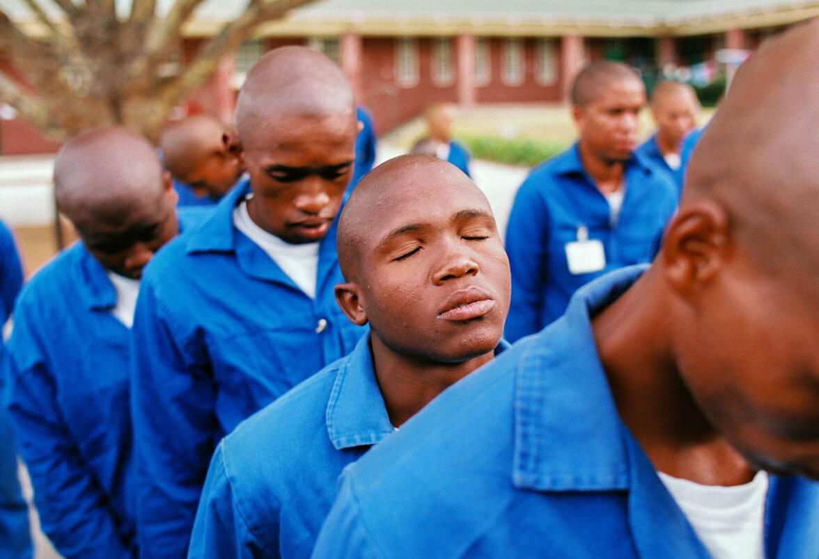 Junge Männer stehen in Blaumännern aufgereiht hintereinander.