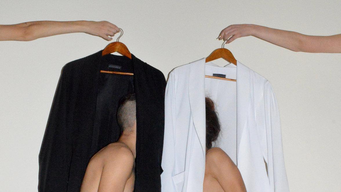 Zwei nackte Menschen stecken ihre Köpfe in eine schwarze und in eine weiße Jacke (Foto: Kostis Fokas)
