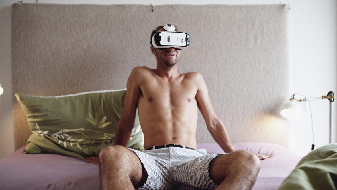 Mann mit VR-Brille sitzt auf Bett