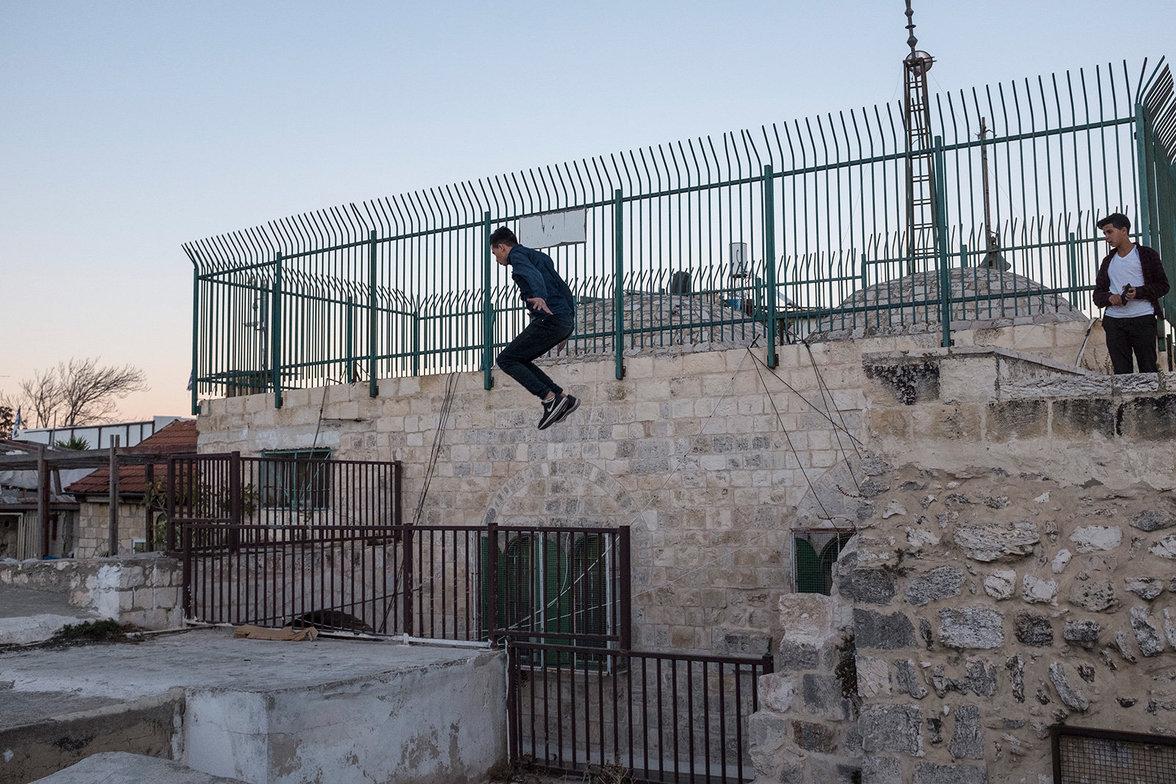 Ein palästinensischer Junge springt geschickt von einem Dach zum nächsten.