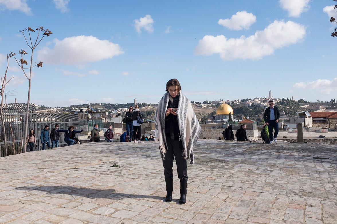 In der Pause eines Foto-Termins auf einem Dach prüft ein Model ihr Smartphone.