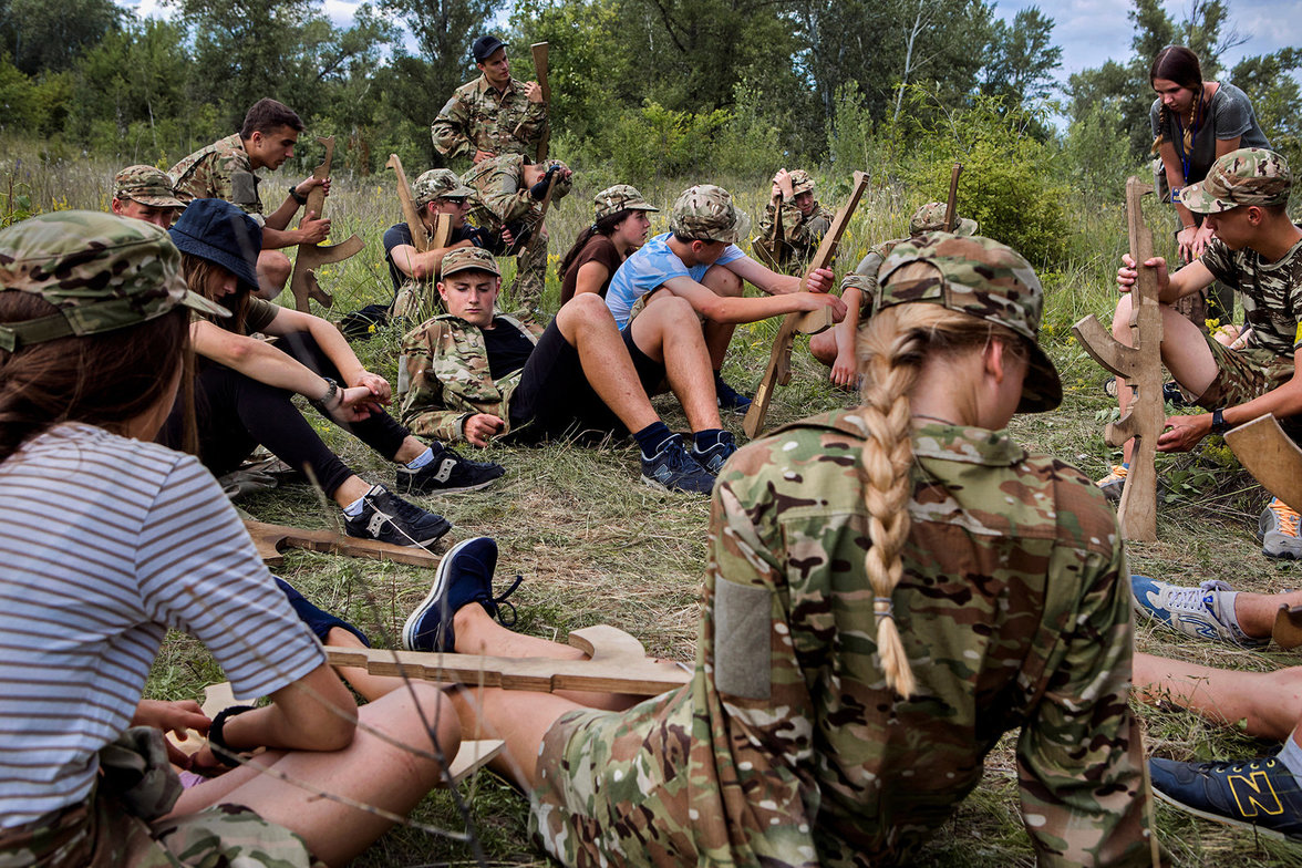 Kinder mit Holzgewehren in Militärkleidung sitzen im Kreis