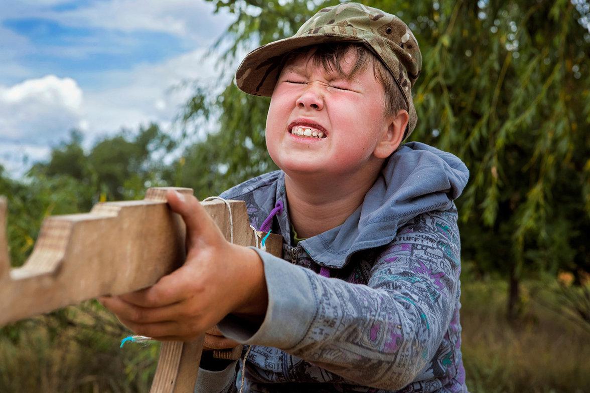 Ein Kind zielt mit einem Holzgewehr