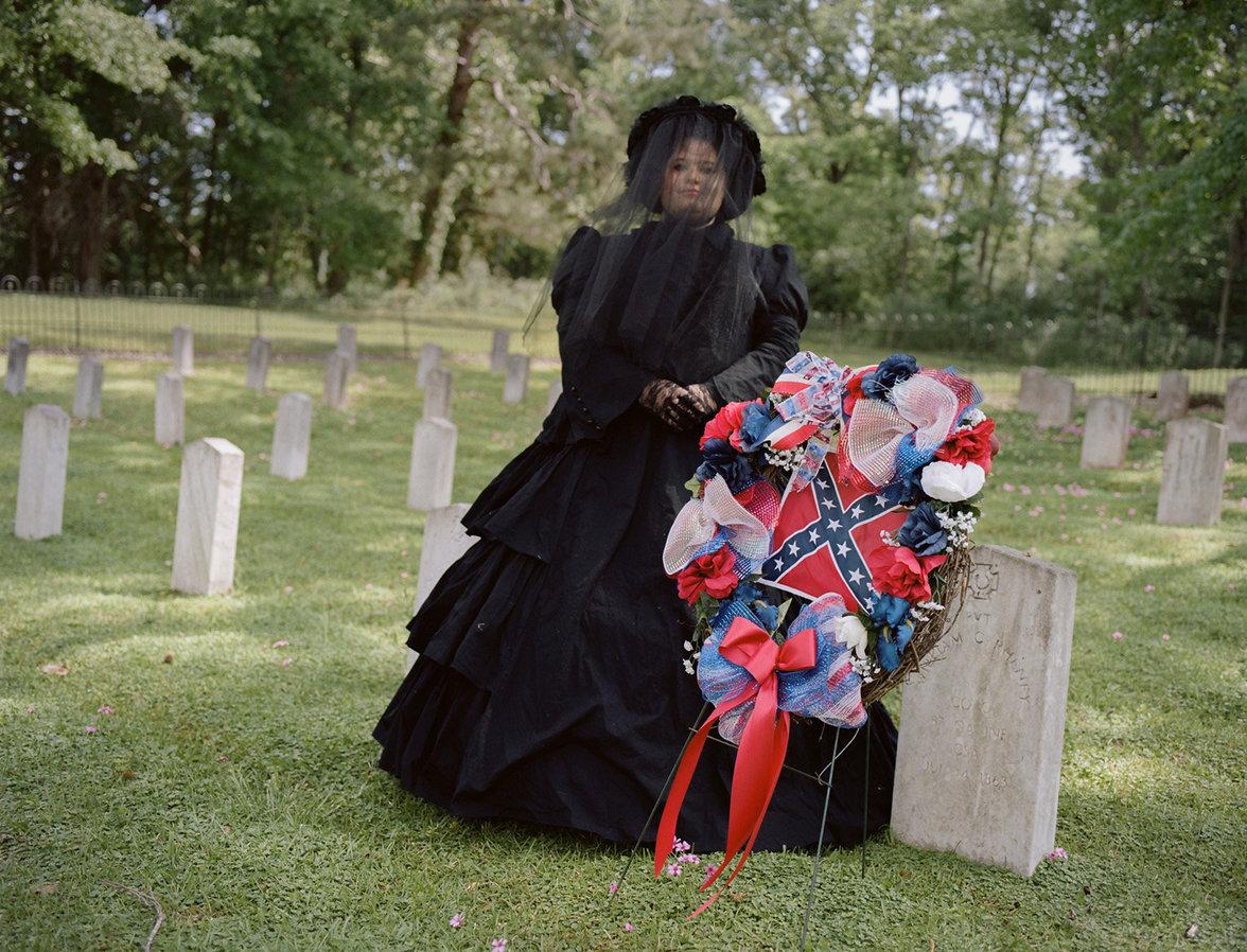Tara Bradley posiert in einem Trauerkleid neben der Kriegsflagge der Konföderierten Staaten von Amerika