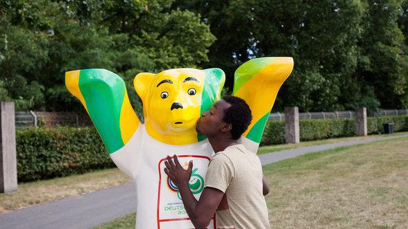 Agomo Atambire küsst einen Buddy Bär