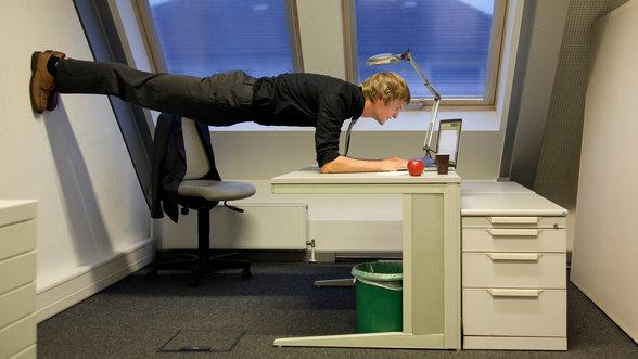 Ein Mann arbeitet in ungewöhnlicher Pose am Laptop