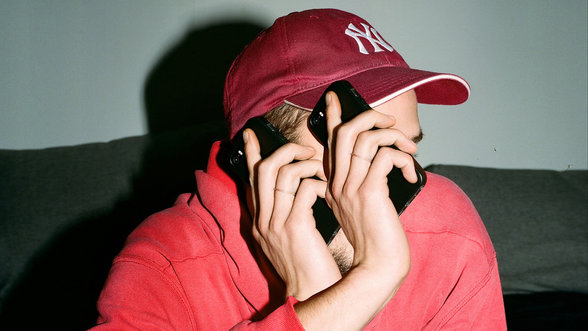 Mann mit 3 Händen und 2 Telefonen