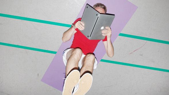 Mann liegt auf der Yoga-Matte und liest im Laptop