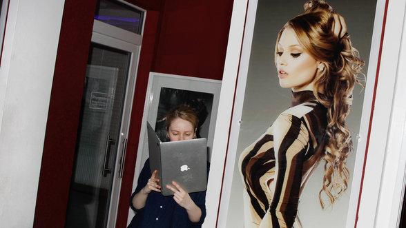 Eine Frau liest in einem aufgeklappten Laptop, das sie wie ein Buch in den Händen hält.