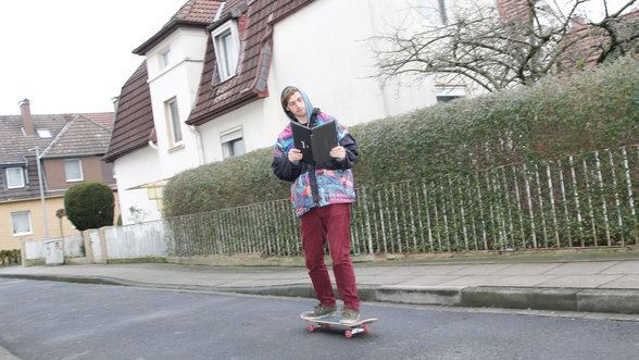 Ein Skater hält einen Laptop, als wäre es ein Buch