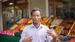 Porträt des fluter-Praktikanten Agomo Atambire aus Ghana vor einem Gemüsestand