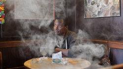 Agomo Atambire, Praktikant bei fluter, sitzt in einer Raucherkneipe