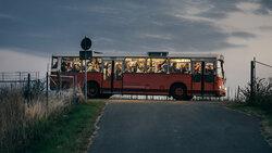 Arbeitskräfte kommen am frühen morgen mit einem alten Bus auf einer Apfelplantage in Sachsen an