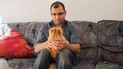 Aziz mit seiner Katze in seiner neuen Wohnung