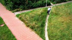Mann läuft auf Trampelpfad neben einem Gehweg