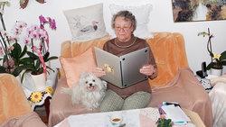 Alte Dame hält einen Laptop wie ein aufgeschlagenes Buch