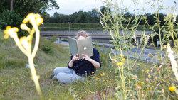 EIne Frau sitzt auf einer Wiese und liest auf dem Laptop wie in einem aufgeklappten Buch