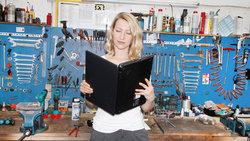 Eine Frau steht in einer Werkstatt und liest in einem aufgeklappten Laptop wie in einem Buch.