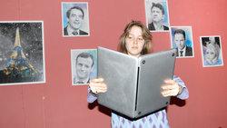 Eine jung Frauen schaut auf einen Laptop, als wäre es ein Buch