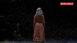 Eine Frau mit rotem Kleid im Wald