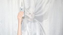 Frau mit iPhone hinter einem Vorhang