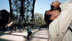 Ein Tourist fotografiert den Eiffelturm von unten