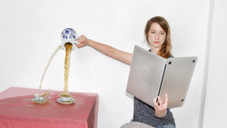 Eine Frau liest in einem laptop wie in einem Buch und vergiesst dabei Tee