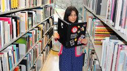Fraus in einer Bibliothek liest in ihrem Laptop