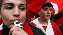 """Ein Teilnehmer einer Demonstration küsst ein  Symbol der """"Grauen Wölfe"""""""