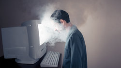 Mann sitz vor rauchendem Computer